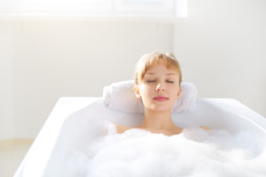 girl relaxing in bathtub on a light background
